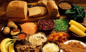 Assortment of foodstuffs with a high fibre content, including various fruits and vegetables, wholemeal bread and baked beans.